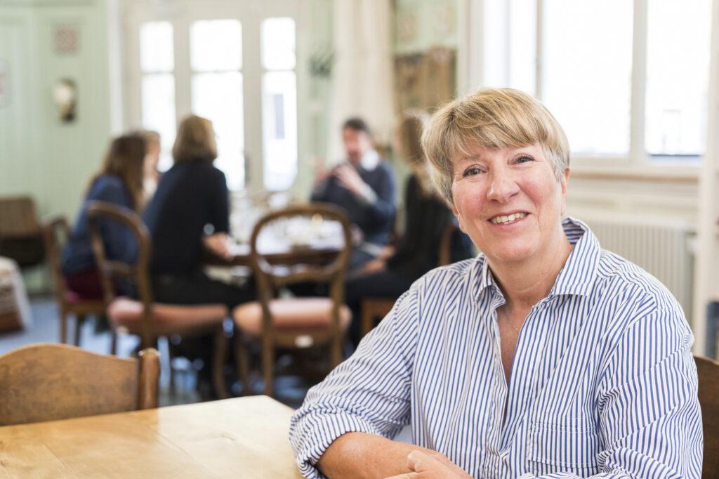 Ursula ist eine frisch gebackene Pensionärin aus Appenzell. Sie sitzt am Tisch am Erzählcafé, im Hintergrund ist die Gruppe in ein Gespräch vertieft.