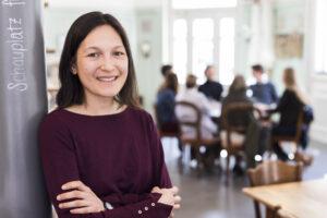 Rhea Braunwalder moderiert seit vielen Jahren Erzählcafés. Sie lehnt an der Wand, während im Hintergrund die Gruppe in ein Gespräch vertieft ist.