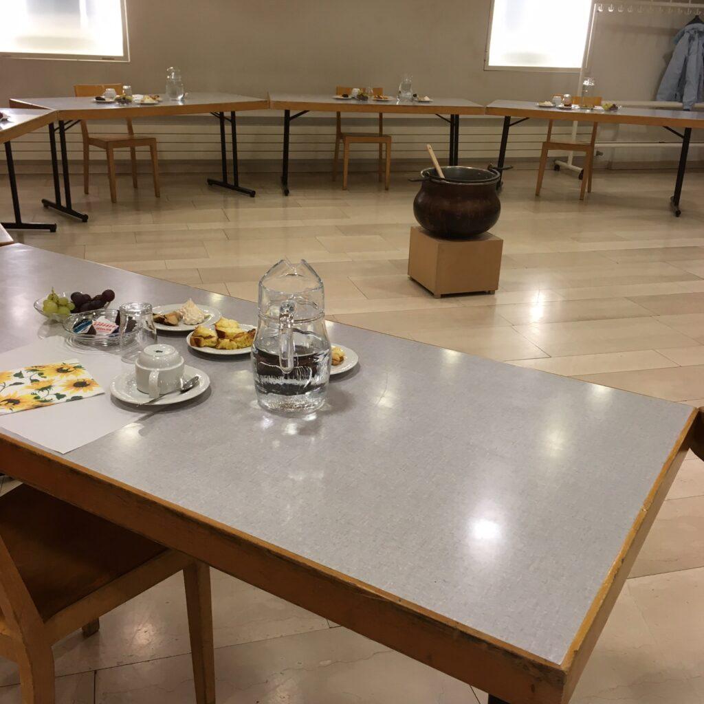 Tische im Kreis gestellt, eine Person pro Tisch, jede ihr Zvieri auf kleinen Tellerchen